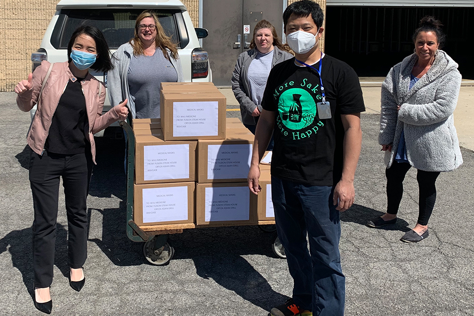 Amy Lin and Jason Wu (wearing masks, from left to right), owners and operators of Fusion Japanese Steakhouse in Morgantown, donate 10,000 medical face masks to WVU Medicine personnel.