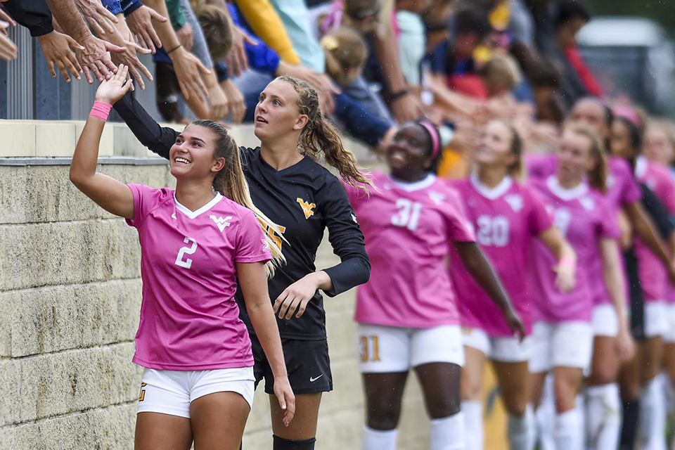 The WVU women's soccer team uses its wide platform to help raise awareness and funding for breast cancer.